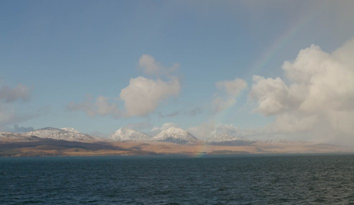 Paps of Jura, Argyll, Scotland, A rainbow and water in the foreground. Snow capped mountains in the background with large fluffy clouds in the sky