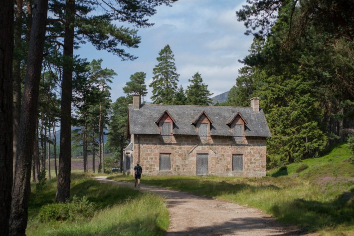 Derry Lodge, Mar Lodge Estate. Man walking passed a brick building with boarding up windows.