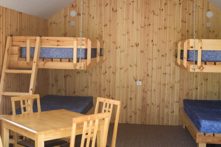 Braemar Caravan Park, Glamping, Cairngorms National Park. Bunk beds and dining table inside camping pod