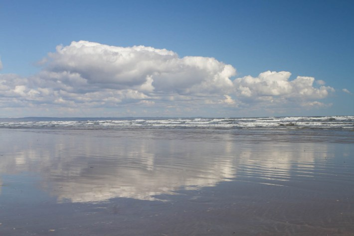 Reflections of clouds on the wet sand