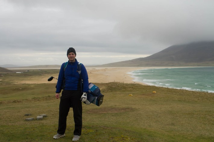 Isle of Harris golf course. Man stood on the golf course, carrying his clubs. The beach and mountains are behind him