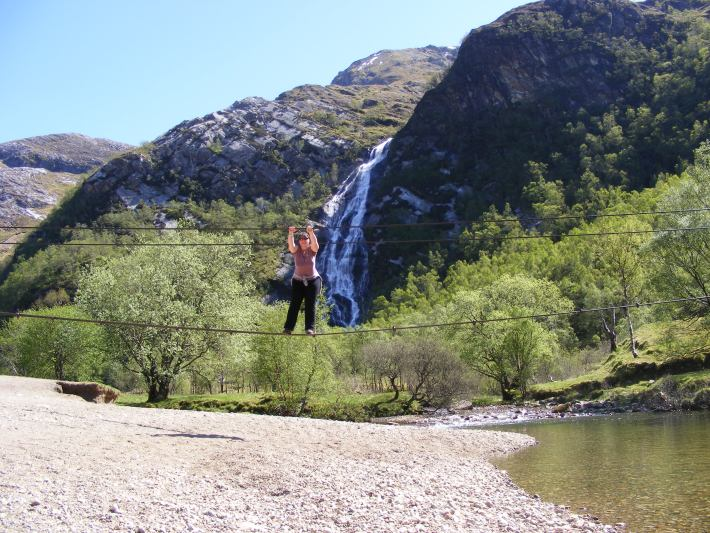 Steall Falls and the wire bridge. Female crossing water on a wire rope bridge. Waterfall in the background