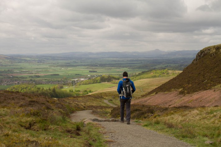 Man walking along trail in the hills in Scotland