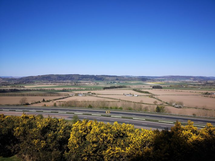Photo of ploughed fields and running left to right across the images is an empty motorway