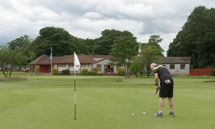 Photo of a man playing golf. He is putting on the 18th green