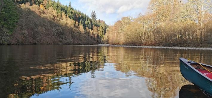Photo of the river Garry in Scotland. The trees have no leaves on as it's winter. To the right of the image is the front of a canoe