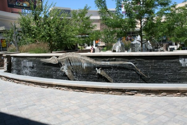 Ichthyosaur skeleton statue with waterfall in background.