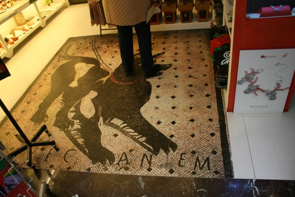 """Iconic mosaic floor from Pompeii cautioning to """"Beware of Dog""""  Turned into a mat in this store."""