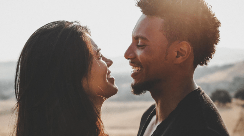 Smiling couple with sea behind
