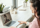 Young woman wearing facemask talking via a laptop video call with a health care professional, also in a facemask