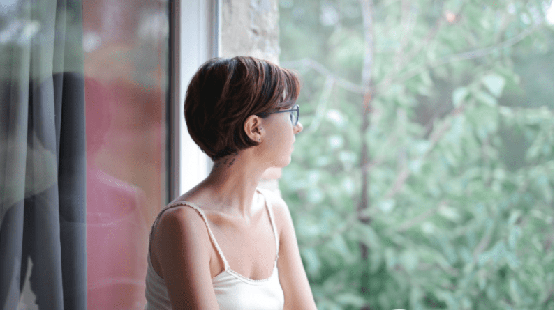 Young woman looking through window pensively