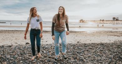 Two young women walking along a pebbled beach laughing