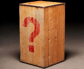 Old wooden crate with a photoshopped question mark on dirty concrete floor.