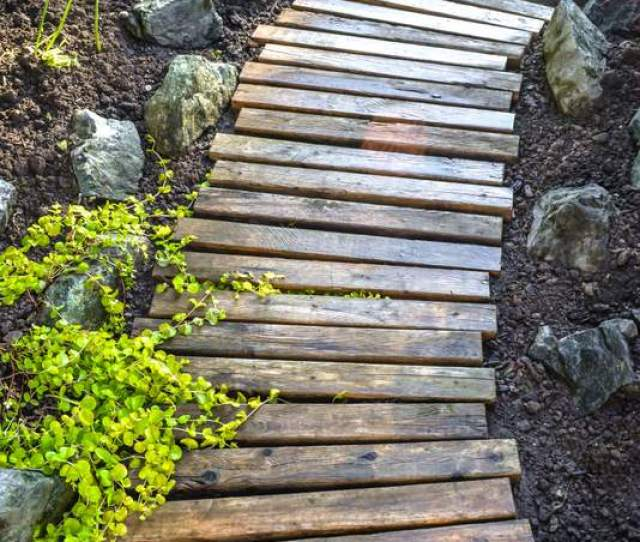 A Gently Curved Rustic Reclaimed Wood Garden Walkway That Really Enhances Flowerbeds