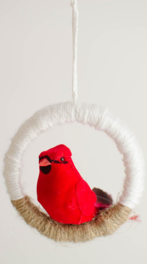 This bird ornament is so pretty and super easy to make. Use your leftover mason jar lids and some yarn, plus an inexpensive craft bird from the Dollar Tree and you're all set! Click through to see how to make this easy mason jar lid ornament.#DIYChristmasOrnaments #HandmadeHolidays #CardinalLove