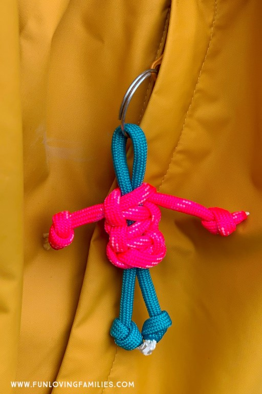 Pink and teal lanyard buddy hanging from zipper.