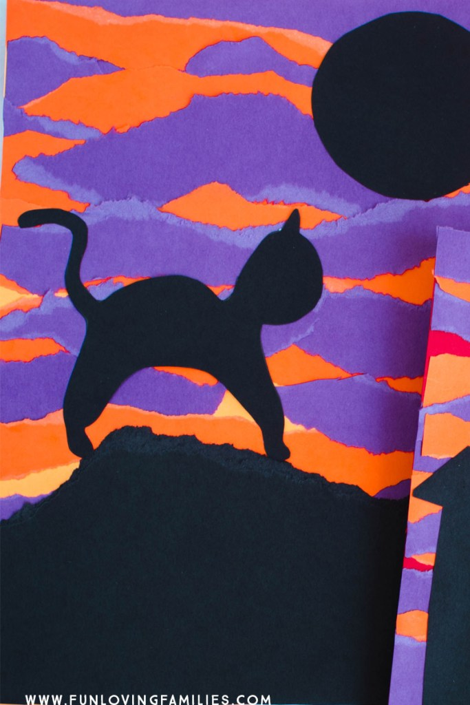 black cat on purple and orange torn paper background