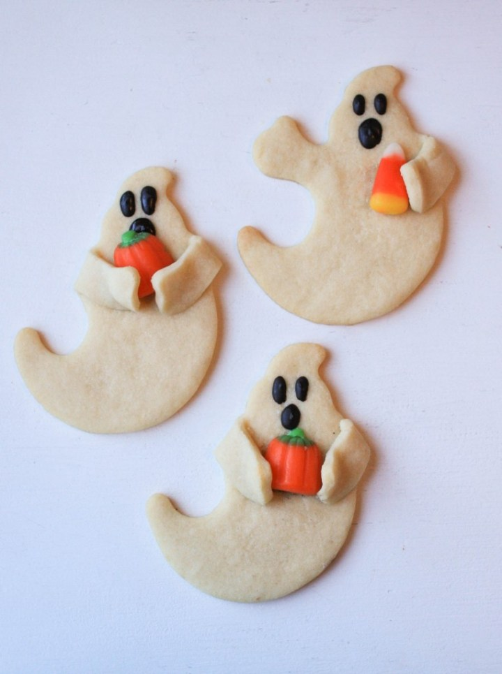 ghost cookies holding candy corns