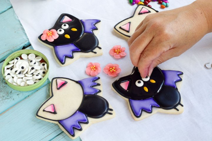 person putting eyes on bat shaped halloween cookies