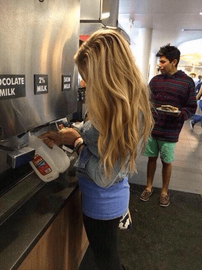 Girls fills milk jug from restaurant milk machine