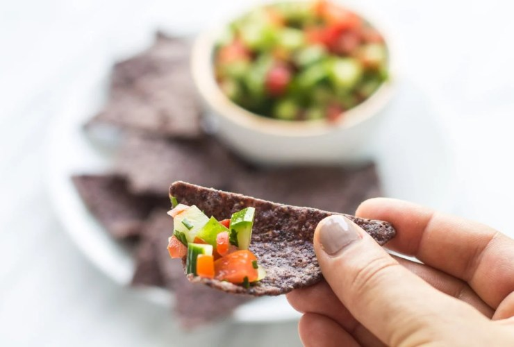 Close up shot of blue corn chip filled with low FODMAP salsa