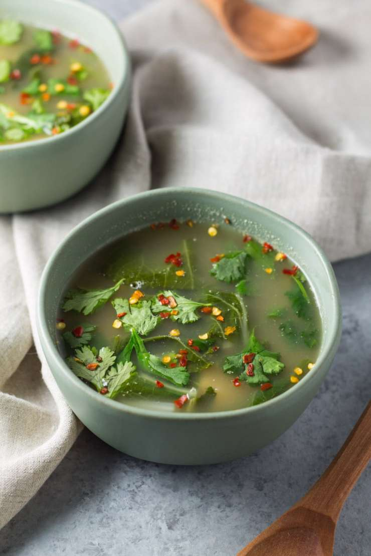 Two bowls of tom yum soup with wooden spoons