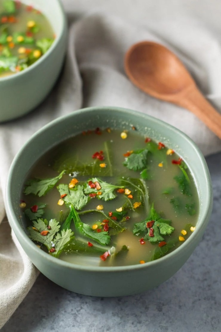 Bowls of Tom Yum soup with a wooden spoon