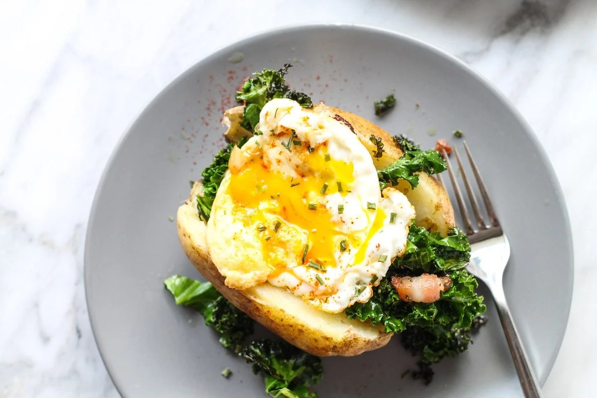 A quick and easy meal anytime of the day, this Low FODMAP Breakfast Stuffed Potato recipe is filled with bacon-y kale and topped with an ooey-gooey egg.