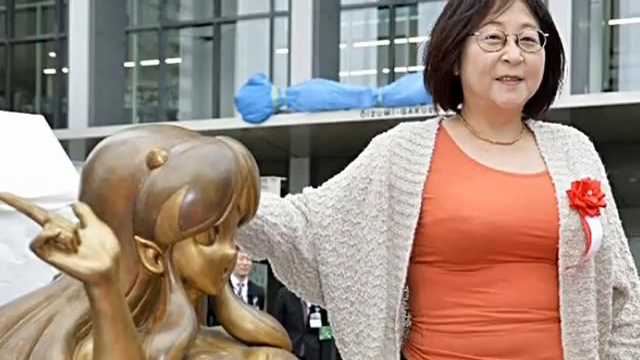 Rumiko Takahashi standing by a statue of Lum, one of her creations.