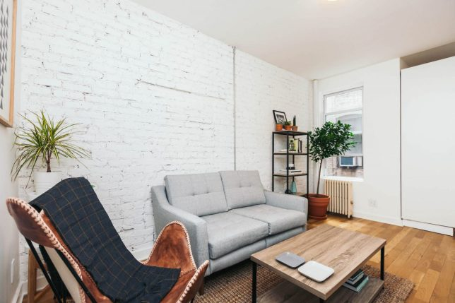 Living room with grey sofa, butterfly chair and white brick wall
