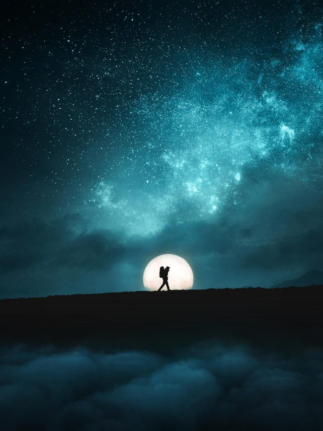 silhouette of person hiking in front of moon