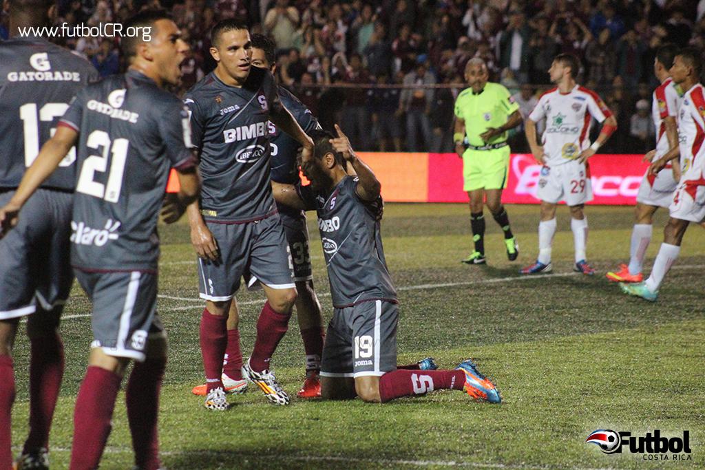 """Soto celebra de rodillas, mientras, Diego Estrada grita al público """"soy morado"""", tras el empate en un gol con el AD Santos"""