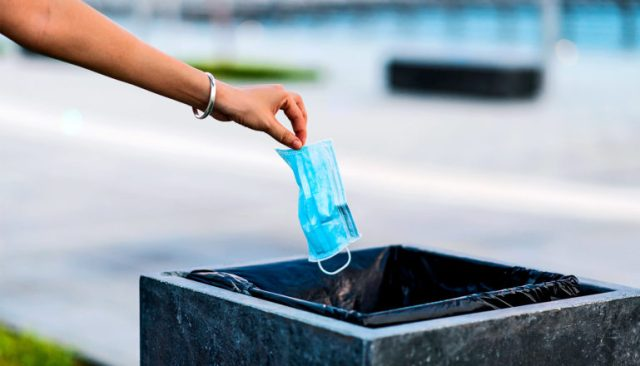 A person drops a blue face mask into a garbage bin