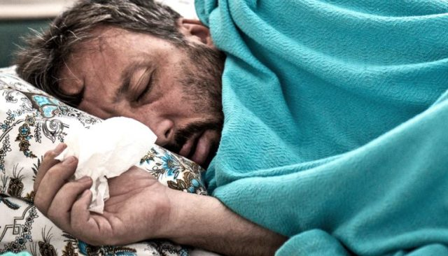 A man holds a tissue while laying under a blue blanket