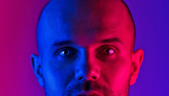 A man's face has pink and blue light shining on it