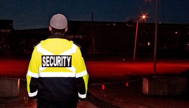 A security guard stands on duty at night near a road