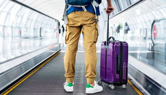 A man stands with a suitcase on a moving sidewalk in an airport