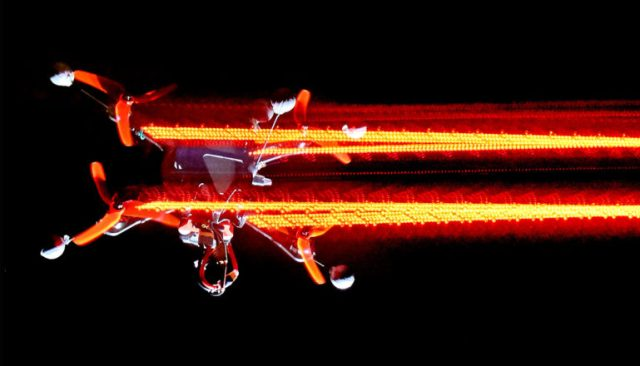 A drone flies fast enough for its lights to blur against a black background