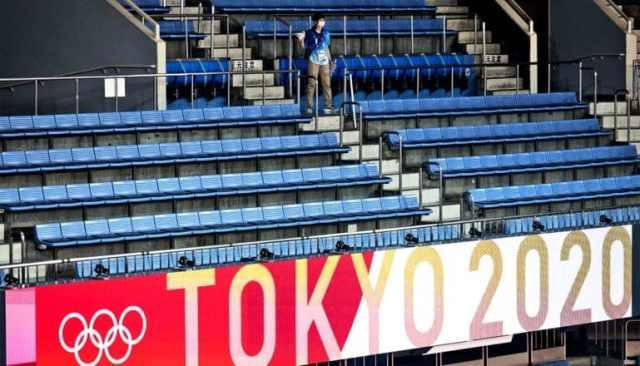 """Een enkele persoon in een zee van lege stoelen op de tribunes bij de Olympische Spelen van Tokyo met een bord """"Tokyo 2020"""" in rood en wit"""