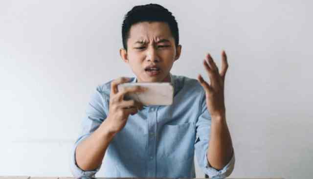 persoon met telefoon ziet er gefrustreerd uit