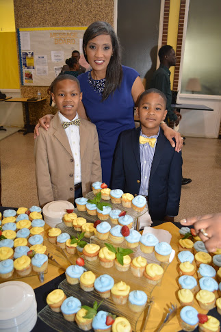 Dr. Marcie Hunt Harris and her sons in front of a row of cupcakes at the120th Anniversary Celebration