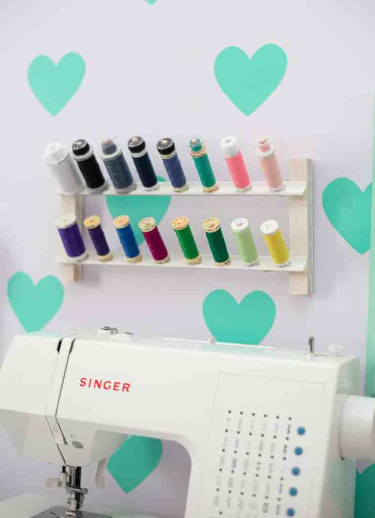 DIY Thread Rack by popular Canada DIY blog, Fynes Designs: image of a DIY thread rack with colorful spools of thread mounted to a wall with light blue hearts painted on it.