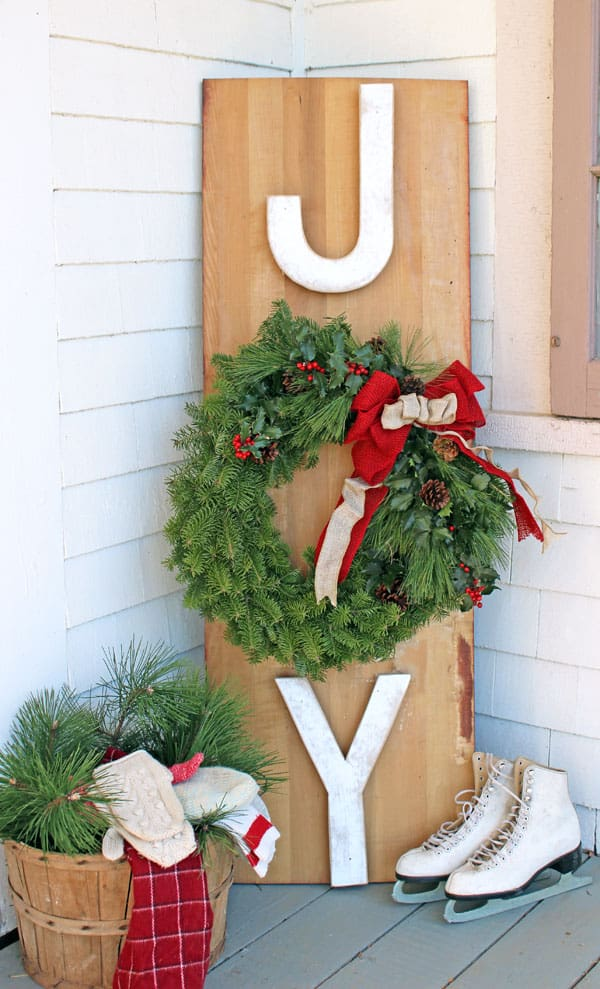 Outside JOY sign. Removable wreath so the sign is usable year after year! |Joy Sign by popular DIY Canada blog: image of a Joy Wreath sign leaning up against a house next to a pair of white ice skates.