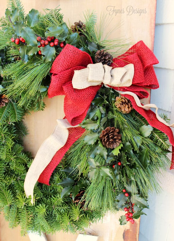 How to decorate your Christmas porch |Joy Sign by popular DIY Canada blog: image of a Christmas wreath with red and neutral burlap ribbons, holly sprigs, and pinecones.