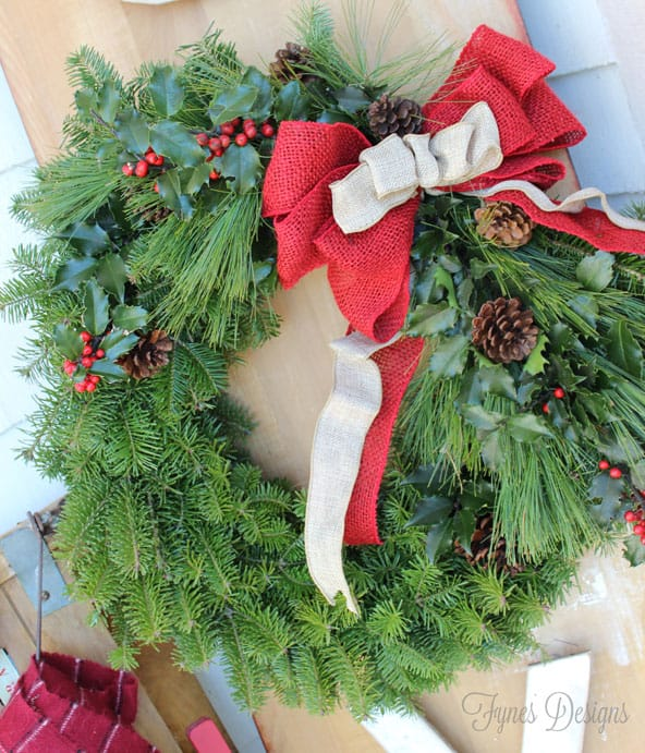 traditional balsam wreath with pine, holly, pinecones with a coloured burlap bow