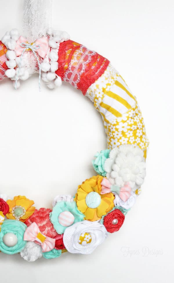 Bright and Fun Spring Wreath #spring #wreath #fabric #diy #yellow #lace #ribbon #fabricflowers   Easy Spring Wreath Idea by popular interior design blog, Fynes Designs: image of a fabric flower spring wreath.