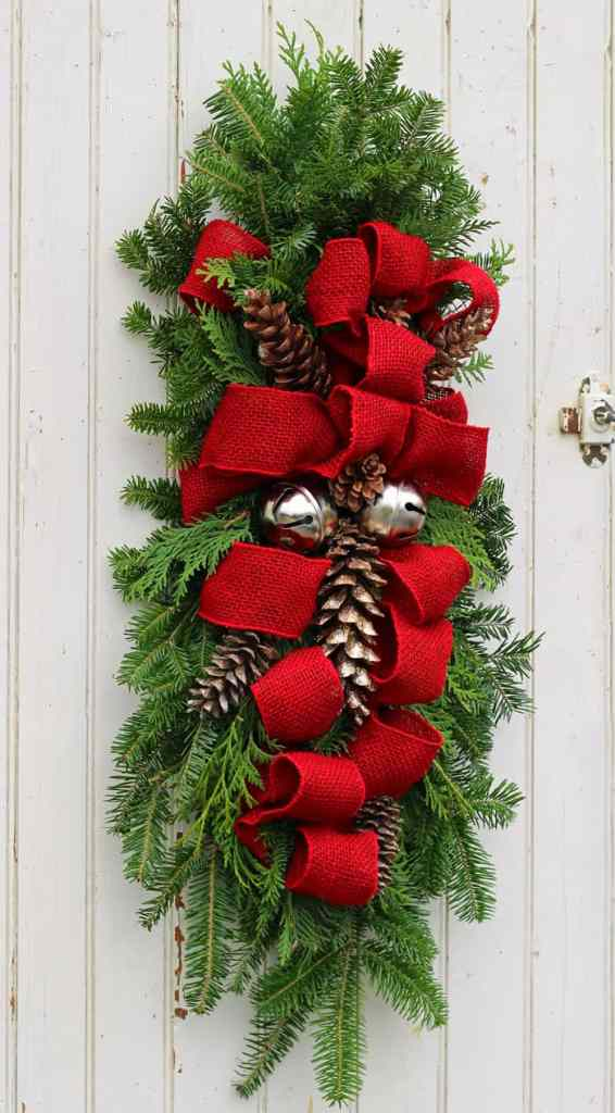 How to make a Christmas swagwreath, Easy to follow instructions featured by top US life and style blog, Fynes Designs | Swag Wreath by popular Canada DIY blog, Fynes Designs: image of a swag wreath with red burlap ribbon, pinecones and silver sleigh bells.