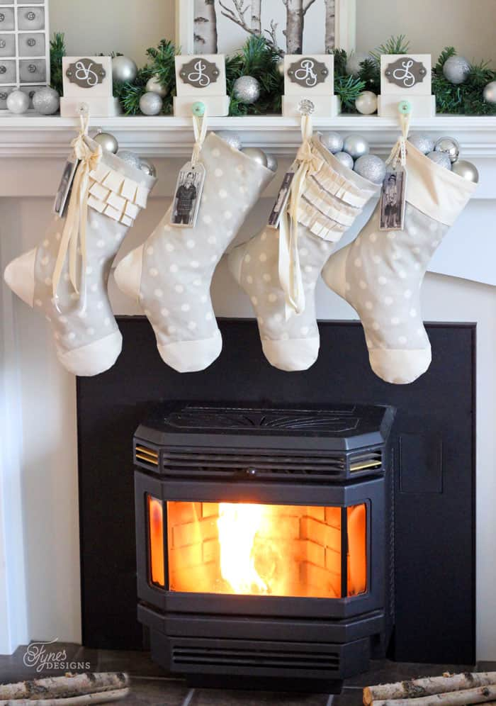 Easy to sew personalized Christmas stocking tutorial  DIY Personalized Christmas Stockings by popular Canada DIY blog, Fynes Designs: image of grey and white stockings filled with silver christmas ornaments and hanging from a white fireplace mantle.