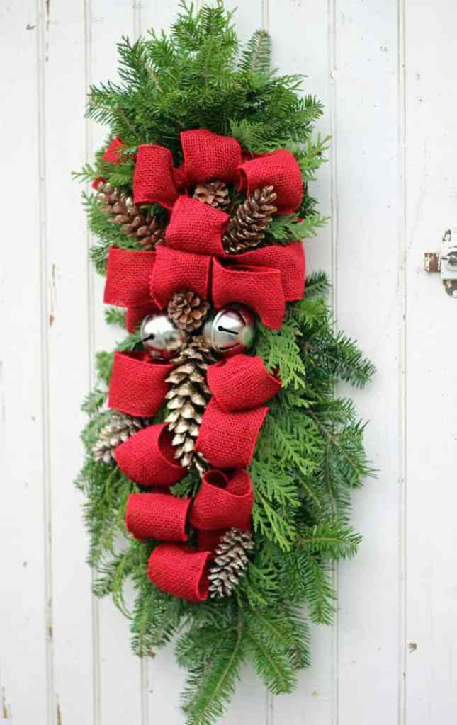 How to make a Christmas swagwreath, Easy to follow instructions featured by top US life and style blog, Fynes Designs |Swag Wreath by popular Canada DIY blog, Fynes Designs: image of a swag wreath with red burlap ribbon, pinecones and silver sleigh bells.