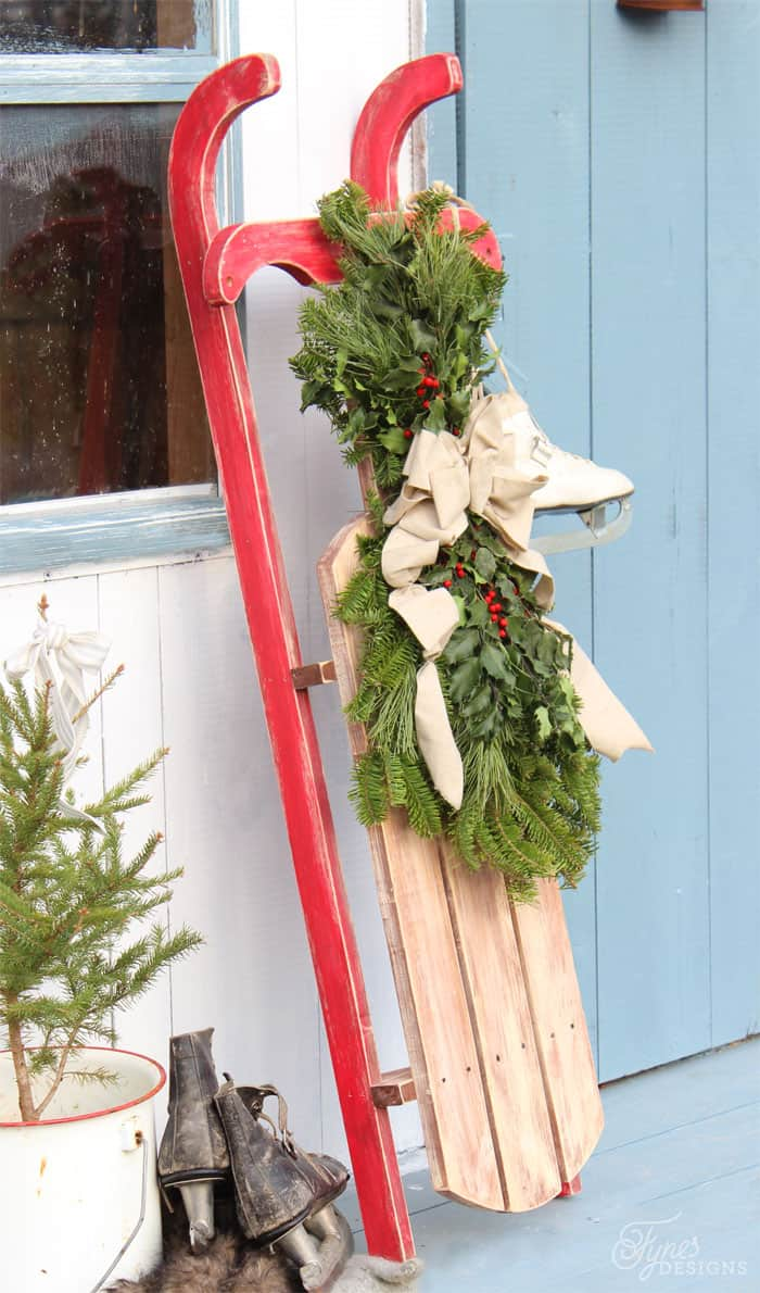 $10 DIY Wooden Sled Tutorial featured by top US craft blog, Fynes Designs: Easy to build vintage sled |DIY Wooden Sled by popular Canada DIY blog, Fynes Designs: image of a vintage inspired DIY wooden sled with a Christmas wreath and pair of white ice skates hanging from it as it leans up against the side of a house.